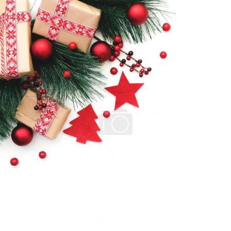Christmas background. Fir tree branch and red christmas decorations on white background. Top view with copy space.