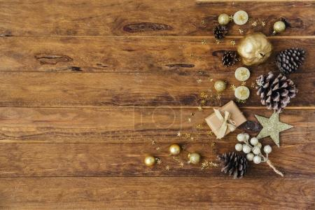 Christmas background with pine cones and gift box on wooden table. Copy space, top view