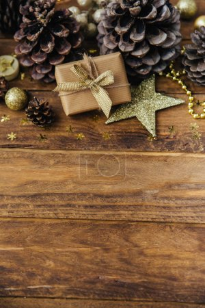 Christmas background with pine cones and gift box on wooden table.