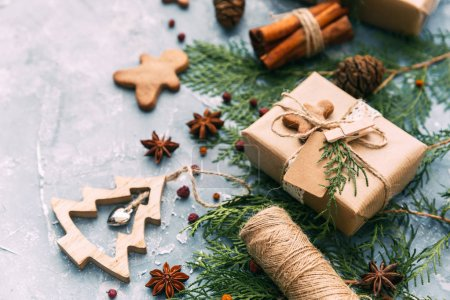 Creative DIY hobby background. Handmade christmas present, box in craft paper with natural decorations. Top view, copy space