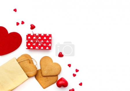 Valentine's Day flat lay. Gift box, cookies and hearts isolated on white