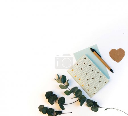 Flat lay composition with notebook and green leaves. Wedding planing or preparations