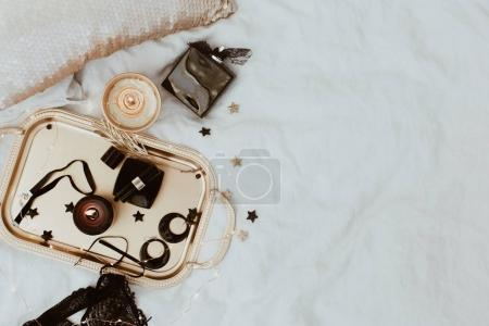 Flat Lay in bed with woman accessories on grey linen. Gold and black luxury stylish objects