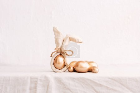 Still Life Happy Easter Background. Gold eggs and linen napkin with decorations