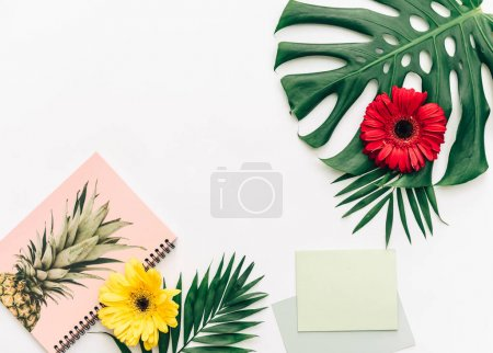 Flat lay Minimal with tropical leaves , flowers and notepad.