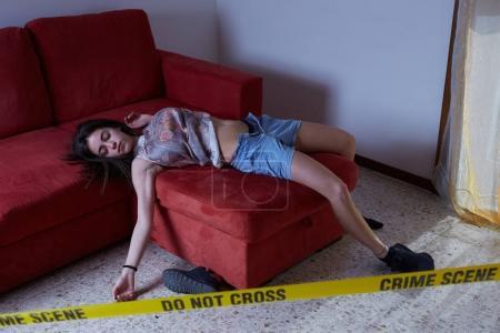 Crime scene imitation. Lifeless woman lying on the floor