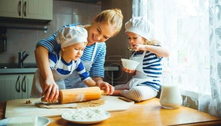 Photo for Happy family in the kitchen. mother and  children preparing the dough, bake cookie - Royalty Free Image