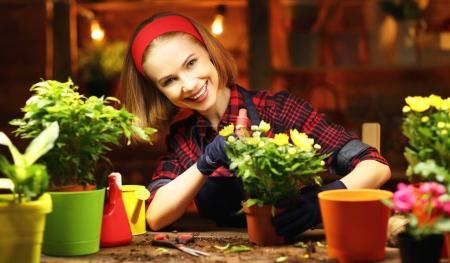 Photo pour Femme heureuse jardinier greffes et fleurs d'arrosage en greenhous - image libre de droit
