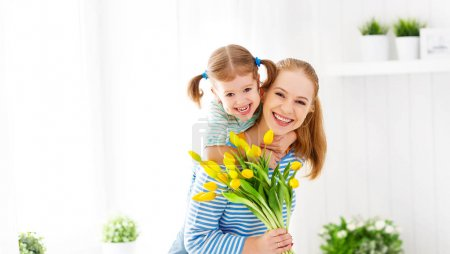 Photo for Happy mother's day! Child daughter congratulates moms and gives her a postcard and flowers tulip - Royalty Free Image