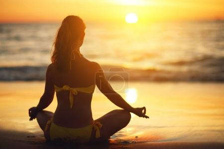 Photo for Woman practices yoga and meditates in the lotus position on the beac - Royalty Free Image