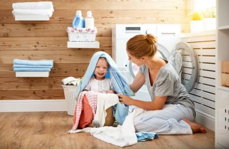 Photo pour Happy famille mère femme au foyer et les enfants dans la buanderie charger une machine à laver - image libre de droit