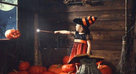 Photo pour Halloween. petit enfant sorcière évoque avec livre de sorts, baguette magique et la citrouille - image libre de droit