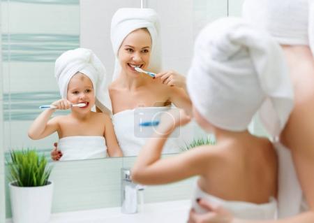 Photo pour Mère et fille se brossent les dents avec une brosse à dents dans la salle de bain - image libre de droit