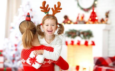 Photo pour Mère de famille heureuse et fille donnant le cadeau de Noël et embracin - image libre de droit