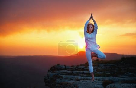 Woman practices yoga and meditates   on sunset mou...