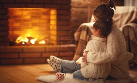 Photo pour Mère de famille et fille enfant câlins et chaud le soir d'hiver près de la cheminée - image libre de droit