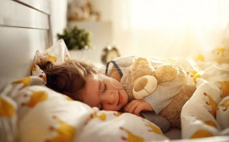Photo for Child  girl sleeps in her bed with a toy teddy bear  in mornin - Royalty Free Image