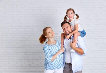 Photo for Happy family mother father and child daughter near an empty brick wal - Royalty Free Image