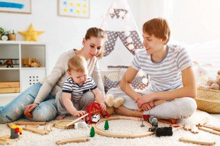 Photo pour Fils-père et bébé famille mère jouant ensemble dans playroo pour enfants - image libre de droit
