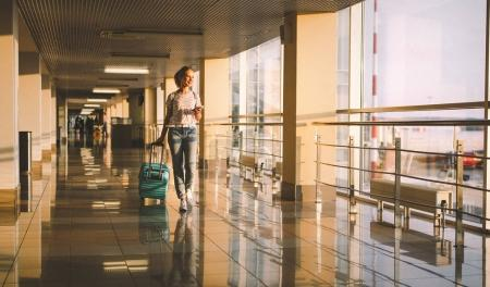 Photo for Young woman goes  at airport  at window  with a suitcase waiting for  plan - Royalty Free Image