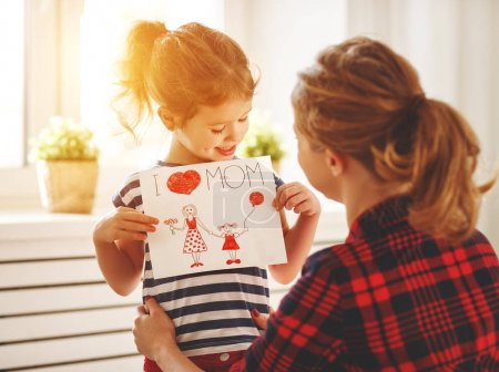 Photo for Happy mother's day! Daughter gives her mother an postcard and hug - Royalty Free Image