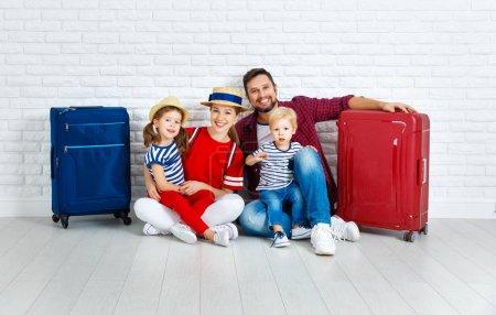 Photo pour Concept voyage et tourisme. famille heureuse avec valises près wal vide - image libre de droit