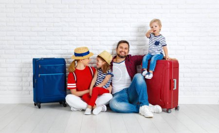 Photo for Concept travel and tourism. happy family with suitcases near empty wal - Royalty Free Image