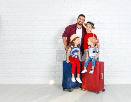 Foto de Concepto de viajes y turismo. familia feliz con maletas cerca wal vacía - Imagen libre de derechos