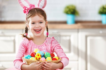 Photo for Happy easter! funny child girl with rabbit ears and a basket  of eggs at home in kitche - Royalty Free Image