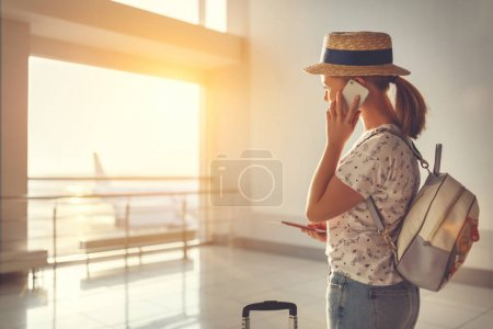 Photo for Young woman waiting for  flying  at airport  at window  with a suitcase - Royalty Free Image