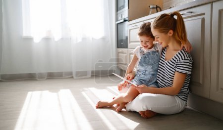 Photo pour Joyeuse fête des mères ! enfant fille félicite sa mère et sur le sol dans la cuisine lire postcar - image libre de droit