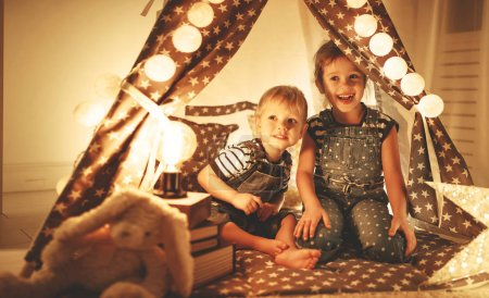 Photo for Happy family loving children brother and sister play, laugh and hug   in dark tent in playroom at hom - Royalty Free Image