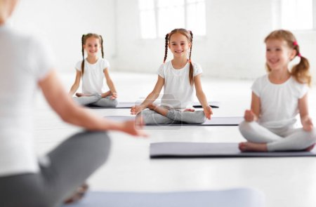 Photo for Children practicing yoga in a lotus pose with a teache - Royalty Free Image