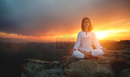 Woman practices yoga and meditates   on mountains,...