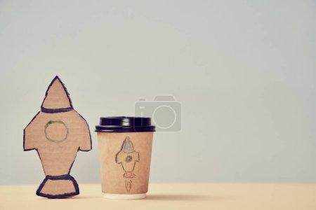 Photo pour Une idée de start-up. Tasse à café en papier avec peinture. Lancez la fusée. Auto-développement. Style maquereau. Copier l'espace dans le côté droit . - image libre de droit