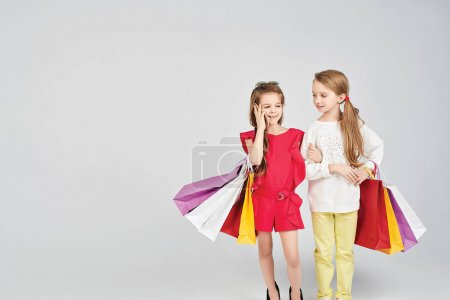 Photo for Young ladies are holding shopper bags. Little girl is calling someone. Shopping, purchases, buy concept - Royalty Free Image