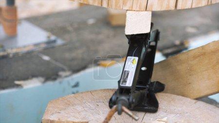 Photo pour Processus de construction d'une maison en bois, concept de menuiserie. Gros plan d'un cric de levage rhombique entre des parties d'une charpente de bois. - image libre de droit
