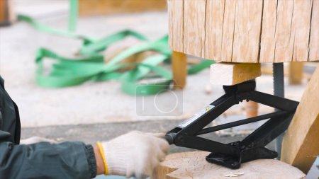 Photo pour Processus de construction d'une maison en bois, concept de menuiserie. Gros plan sur un (e) travailleur-euse qui lâche le cric de levage rhombique entre des parties d'une charpente en bois. - image libre de droit