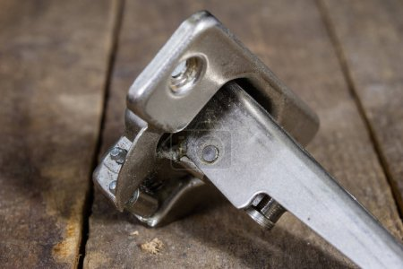 A woodwork hinge on a wooden workshop table. Joinery accessories
