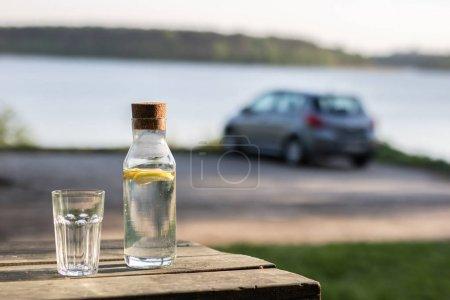 Photo pour Une bouteille d'eau avec du citron et un verre. Tableau au bord du lac. Dans le fond une voiture dans le stationnement. Saison de printemps. - image libre de droit