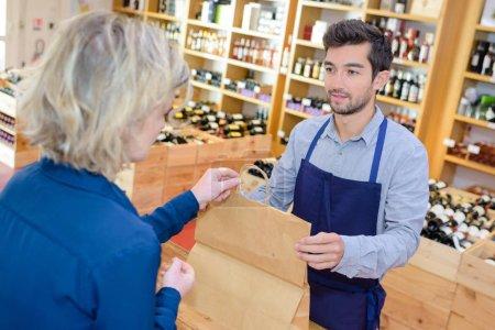 salesman putting wine bottle in paperbag for customer