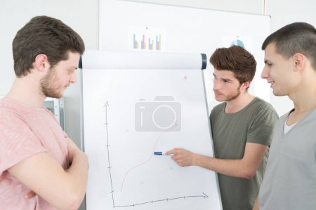 young businessman explaining chart on the whiteboard to his colleagues