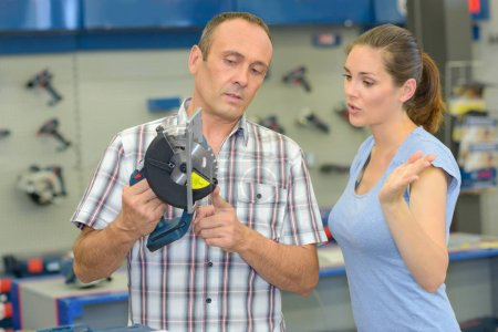 Man and woman looking at circular saw