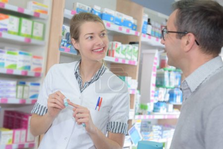 positive female pharmacist counseling customer