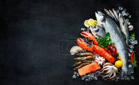 Photo for Fresh fish and seafood arrangement on black stone background - Royalty Free Image