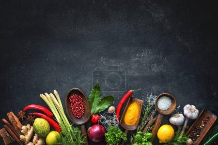 Photo for Various herbs and spices on black stone plate - Royalty Free Image