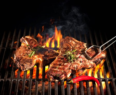 Photo for Beef T-bone steaks on the grill with flames - Royalty Free Image