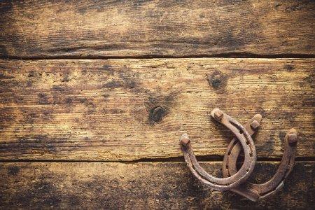 Photo pour Deux vieux fers rouillés sur une planche en bois vintage - image libre de droit