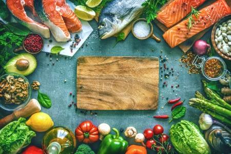 Photo for Assortment of fresh fish with aromatic herbs, spices and vegetables. Balanced diet or cooking concept - Royalty Free Image