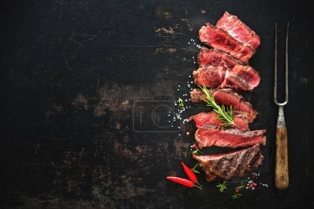 Photo for Sliced medium rare grilled beef ribeye steak on dark background - Royalty Free Image